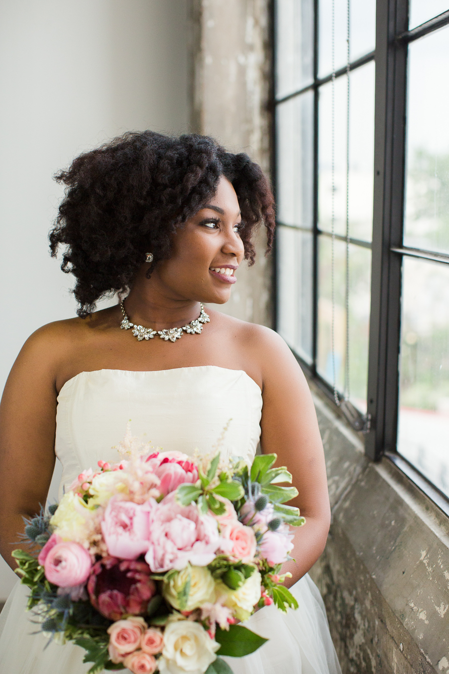 Gorgeous African American bride, wedding hairstyle and a colorful floral bouquet